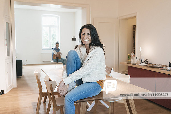 Portrait of smiling woman sitting on table at home