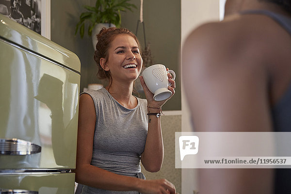 Junges Paar in der Küche sitzend  Kaffee trinkend  lachend