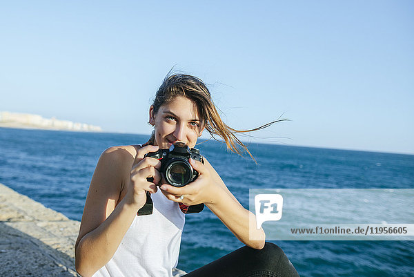 Porträt einer lächelnden jungen Frau mit Kamera am Meer