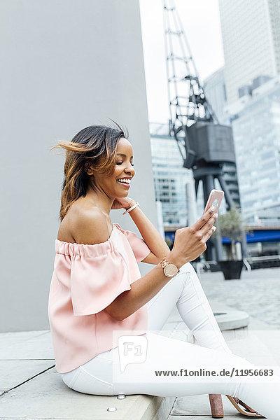Lächelnde Frau sendet Nachrichten mit ihrem Smartphone in der Stadt
