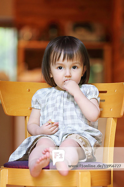 Mixed-race young girl eating on wooden chair