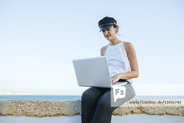 Junge Frau mit Hut mit Laptop im Freien