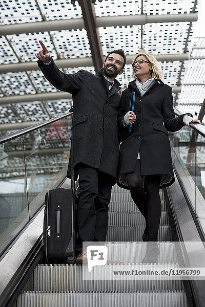 Geschäftsmann und Geschäftsfrau auf der Rolltreppe