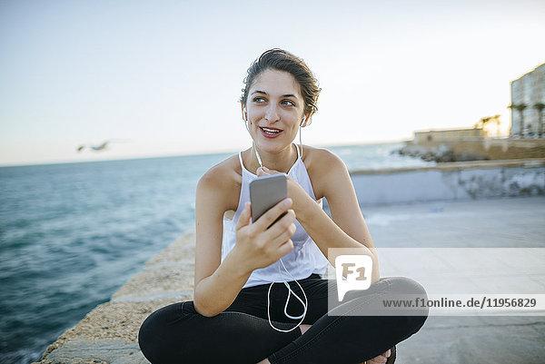 Junge Frau im Gespräch mit Freisprechtelefon an der Strandpromenade