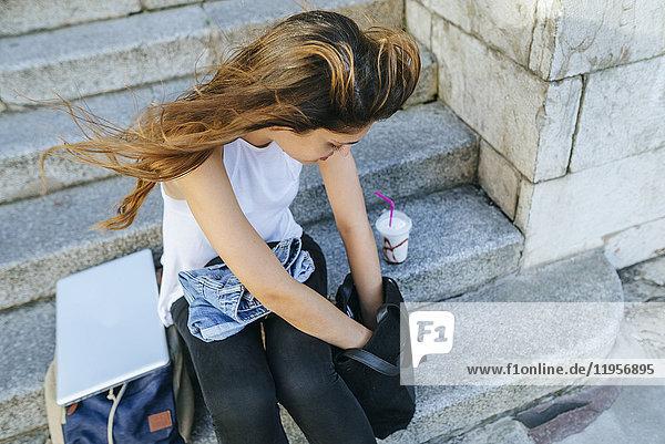 Junge Frau mit Laptop und Smoothie im Rucksack