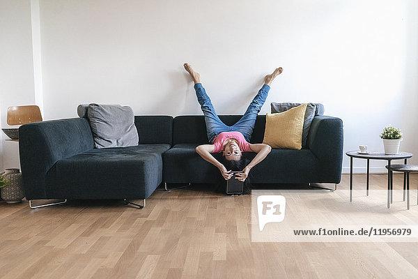 Frau zu Hause mit auf dem Sofa liegender Tablette kopfüber