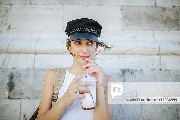 Porträt einer jungen Frau  die einen Smoothie trinkt