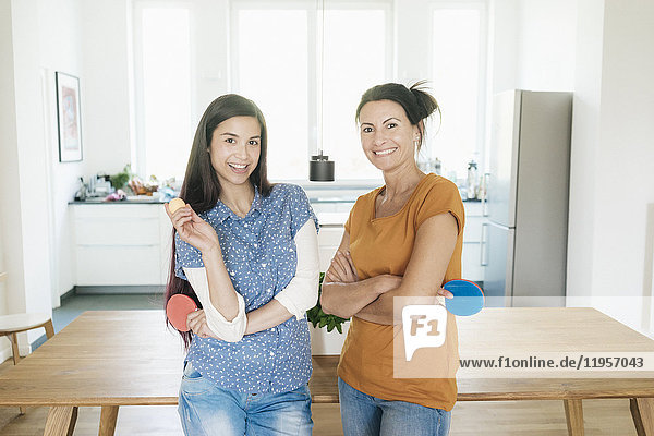 Porträt von zwei lächelnden Frauen mit Tischtennisschlägern zu Hause