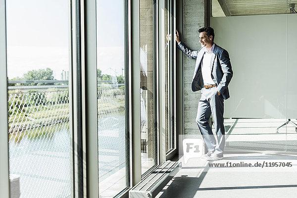 Geschäftsmann am Fenster stehend  mit Händen in den Taschen