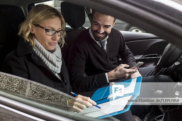 Geschäftsmann und Geschäftsfrau mit Dokumenten im Auto