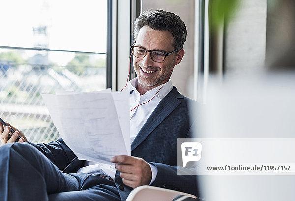 Lächelnder Geschäftsmann am Telefon beim Lesen von Dokumenten