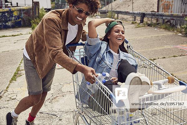 Junger Mann schiebt Freundin im Einkaufswagen sitzend