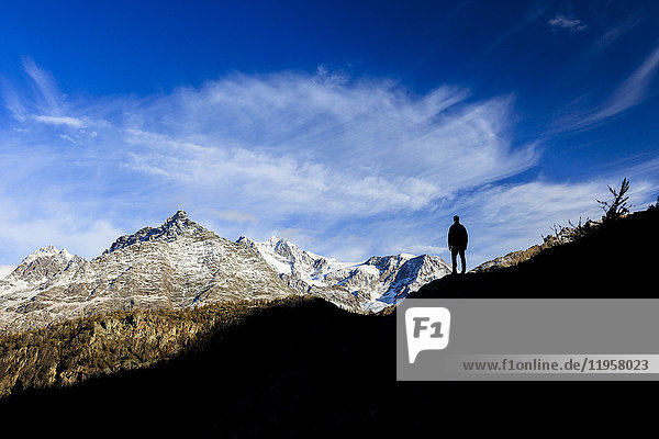Hiker admires Monte Disgrazia from Lake Mufule  Malenco Valley  Province of Sondrio  Valtellina  Lombardy  Italy  Europe