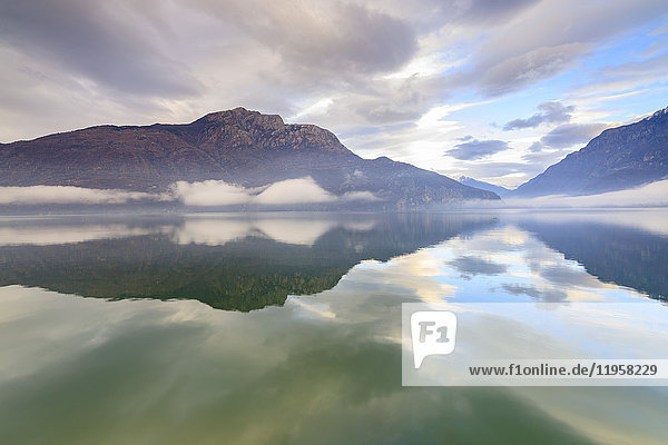Mountains reflected in Lake Mezzola at dawn shrouded by mist  Verceia  Chiavenna Valley  Lombardy  Italy  Europe