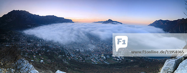 Panoramic of fog at sunrise above the city of Lecco seen from Monte San Martino  Province of Lecco  Lombardy  Italy  Europe