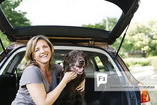 Portrait of woman stroking Labrador Retriever in car trunk