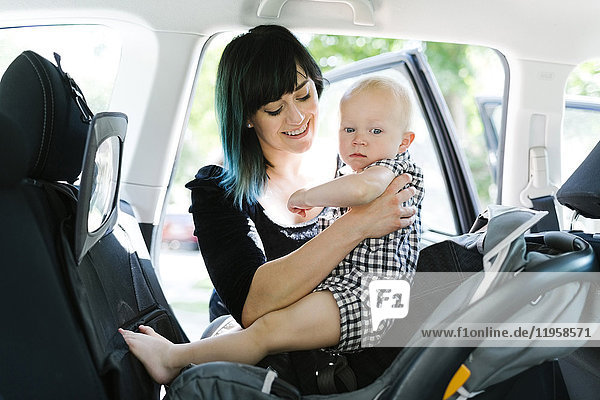 Mother holding baby boy (12-17 months) in car