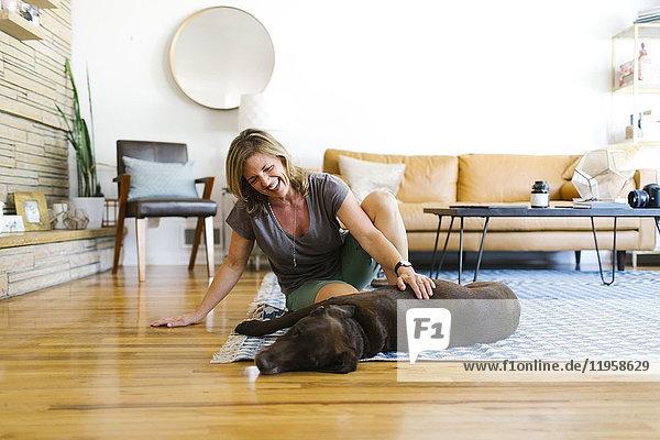 Woman stroking Labrador Retriever in living room