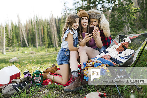 Mother with son (6-7) and daughter (8-9) camping in forest