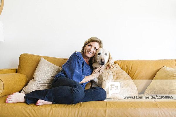 Portrait of woman embracing Labrador Retriever on sofa