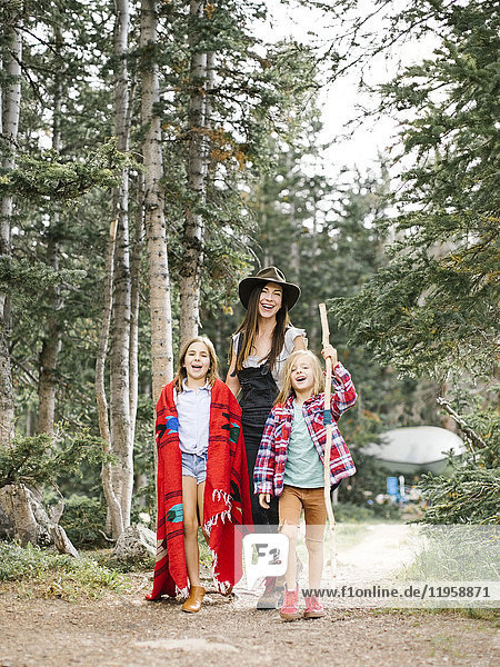Mother with son (6-7) and daughter (8-9) hiking in forest