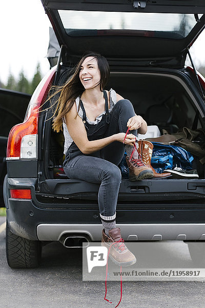 Smiling woman sitting in car trunk and tying hiking shoes