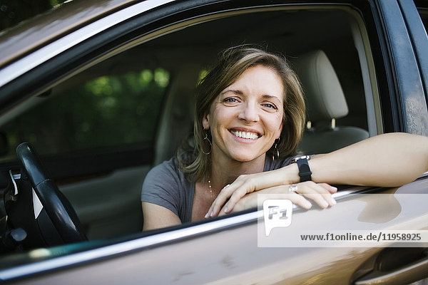Portrait of smiling woman looking through car window