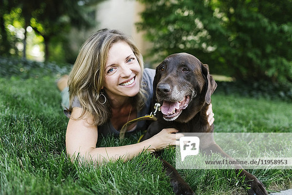 Portrait of smiling woman lying on grass with Labrador Retriever