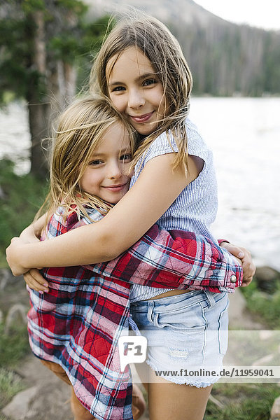 Brother and sister hugging in forest