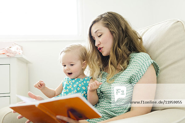 Mother with baby girl (12-17 months) sitting in living room and reading book
