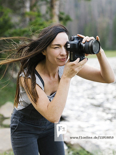 Woman taking pictures by lake