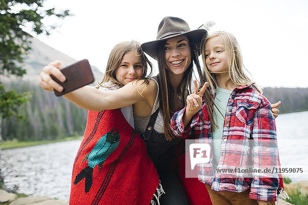 Outdoor portrait of mother with kids (6-7  8-9) taking selfie by lake
