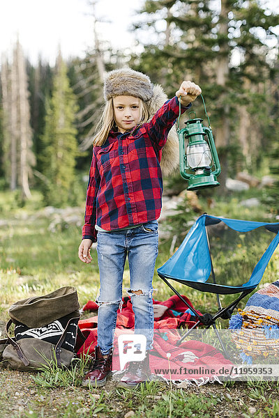 Portrait of boy (6-7) with camping gear in forest