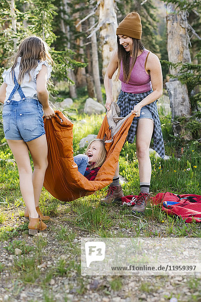 Woman playing in forest with son (6-7) and daughter (8-9)