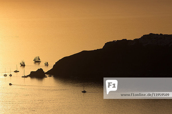 Sunset over the sea with boats and cliffs in silhouette near Oia  from Imerovigli  Santorini  Cyclades  Greek Islands  Greece  Europe