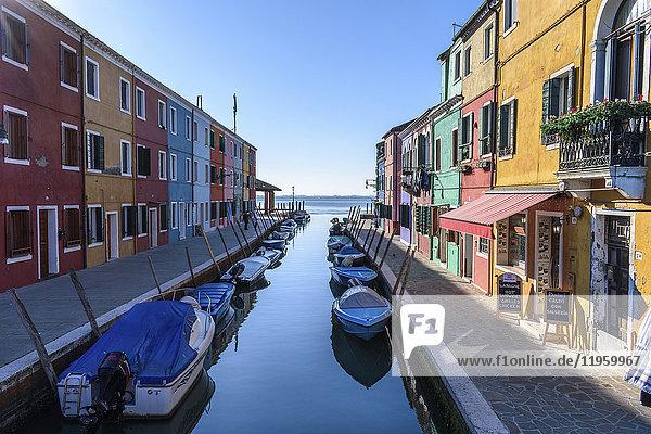Kleine Motorboote vertäut in engen Kanallinien mit bunten Häusern  Venedig  Italien.