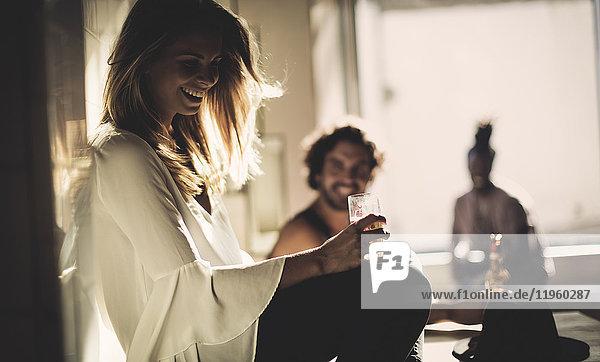 Seitenansicht einer Frau mit langen blonden Haaren  die im Haus sitzt und ein Bierglas hält  im Hintergrund zwei Männer.