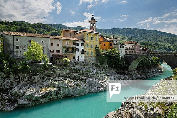 Colorful stucco houses on the turquoise Soca River with stone bridge at old section of Kanal Slovenia with Assumption of Mary church.