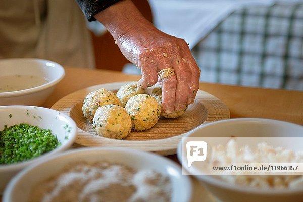 A chef has finished some of homemade dumplings  (canederli)  Bolzano province  South Tyrol  Trentino Alto Adige  Italy .