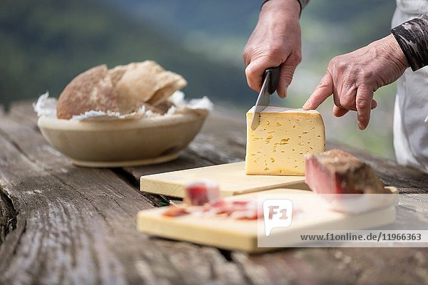 A chef is cutting a piece of cheese  Bolzano province  South Tyrol  Trentino Alto Adige  Italy .