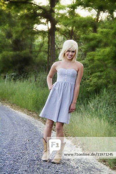 A young woman walking outdoors on a rural gravel road in Spokane County  Washington  USA.