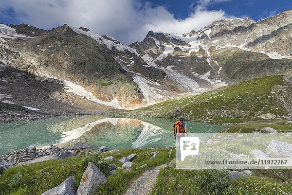 A girls walks near the Locce Lake at the foot of the East face of Monte Rosa Massif (Locce Lake  Macugnaga  Anzasca Valley  Verbano Cusio Ossola province  Piedmont  Italy  Europe).