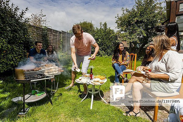 A Young Man Cooking Food At A Traditional Family Barbecue  Sussex  UK.
