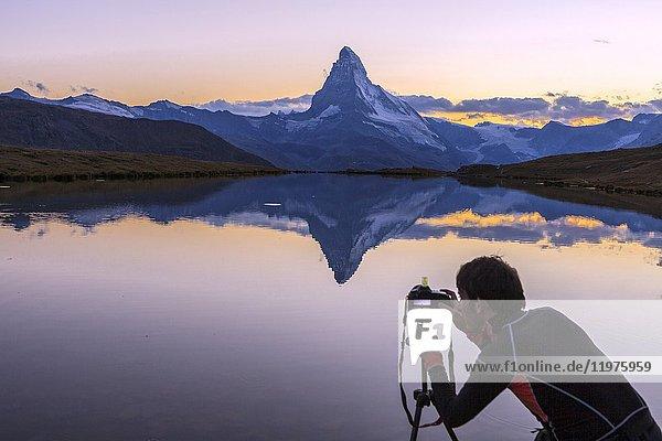 The photographer captures the Matterhorn at sunrise from Stellisee. Zermatt Canton of Valais Pennine Alps Switzerland Europe.