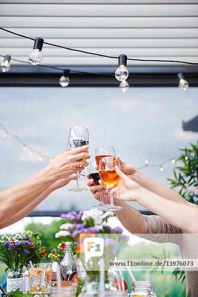 Hände von Männern und Frauen  die am Tisch im Hof auf den Wein anstoßen