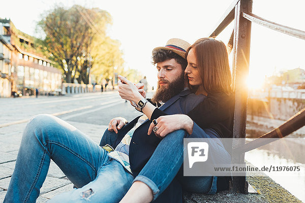 Hipster couple sitting looking at smartphone by city canal