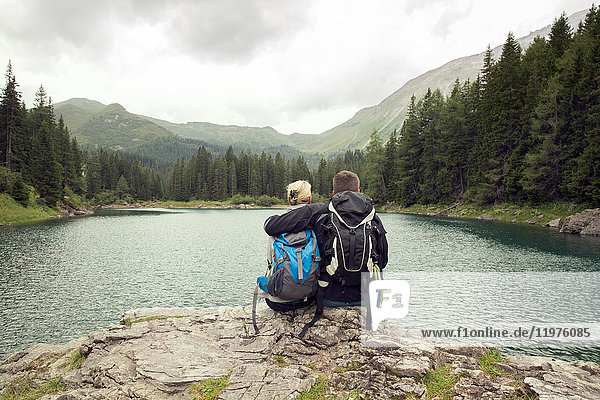 Rear view of couple hiking  sitting by lake  Tirol  Steiermark  Austria  Europe