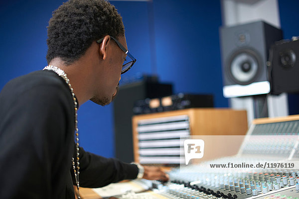 Young male college student at sound mixer in recording studio