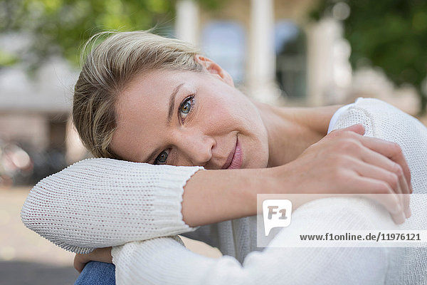 Porträt einer Frau  die die Knie umarmt und lächelnd in die Kamera schaut