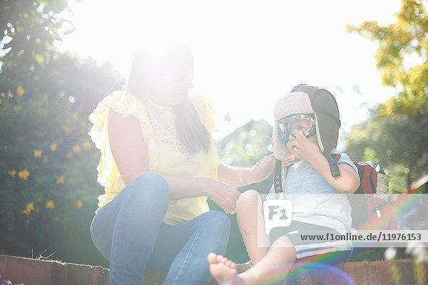 Junge mit Mutter im sonnenbeschienenen Garten setzt Piloten-Fliegerbrille auf